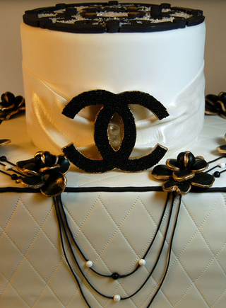 Stunning Chanel cake in white and black decor and large Chanel logo.PNG