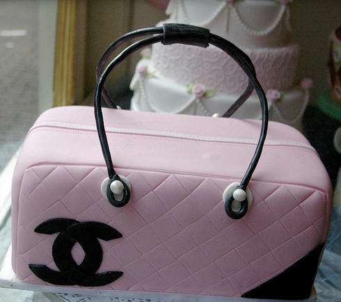 Beautiful Chanel purse cake in light pink and black patterns and Chanel logo.PNG