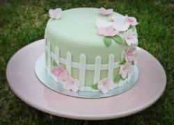 Mother's Day cake with garden theme cake in green with white fence and pink flowers.JPG