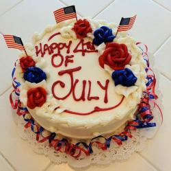 Celebration 4th of July cake decorated with flags and roses in red and blue.JPG