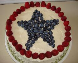 Healthy 4th of July cake decorated with fresh berries and blue berries shaped into a large star.JPG