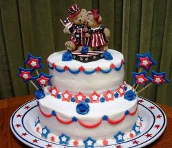 Two tiers 4th of July cake with bears cake toppers holding US flags.JPG