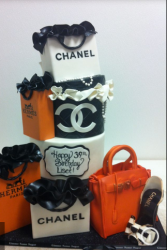 Chanel shopping bags in white and black cake with orange Hermes handbag.PNG
