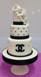 White and black Chanel wedding cake with Chanel logo cake decor with cake flowers.PNG