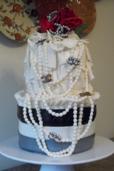 Chanel cakes with Chanel pearls and crystal Chanel logo with red roses cake toppers.PNG