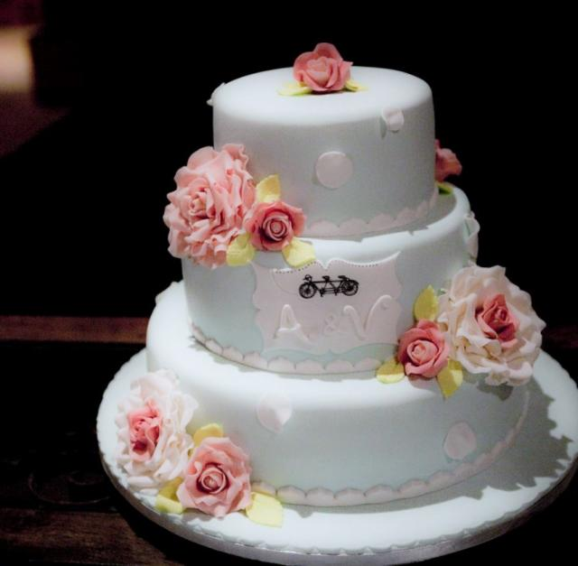 Light green medium size 3 tier wedding cake with monogram on second tier plus fresh pink roses.JPG