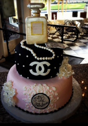 Beautiful pink and black Chanel cake with Chanel perfume cake topper and pearl neckles.PNG