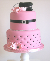 Large pink Chanel cake with black Chanel purse cake topper with light pink flowers.PNG