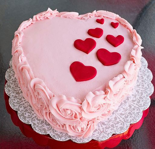 Heart shaped pink Valentines Day with red hearts cake ...