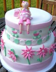 Two tier baby shower cake with pregnant woman on top.JPG