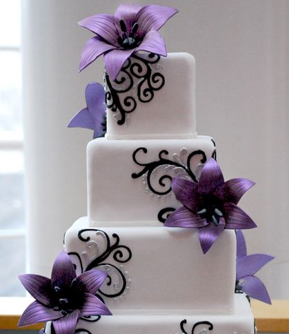 Four tier white cubic wedding cake with purple flower petals.JPG