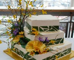Three tier white rectangular wedding cake with yellow daisey flowers and branches.JPG
