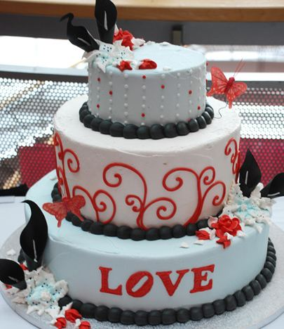 Three tier round white wedding cake with black beads and the word LOVE in red.JPG