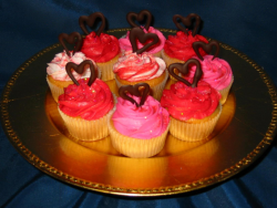 Valentine cupcakes in bright colors with chocolate heart topper.PNG