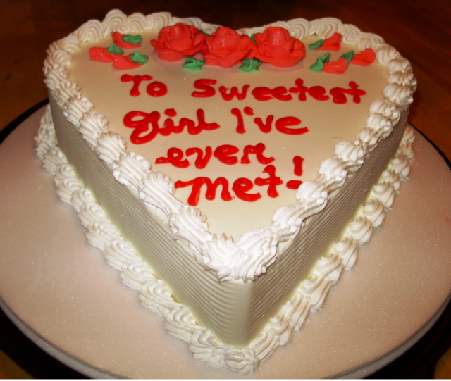 White valentine cake in heart shape with red flowers.PNG