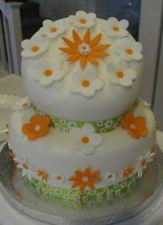 Two tier topsy turvy round white cake with orange and white flowers.JPG