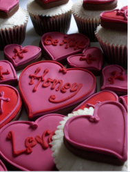 Bright pink heart shape cup cakes with letters.PNG