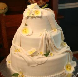 White 3 tier wedding cake with draps and lillies.JPG