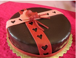 Round valentine chocolate cake with red ribbons cake decor.PNG