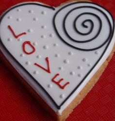 Heart shaped white Valentines cake with black swirl with the word LOVE.JPG