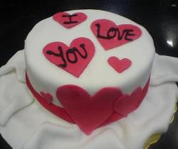 White Valentine's cake with I Love You in hearts.JPG
