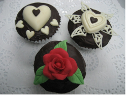 Three dark chocolate valentine cup cakes with cute decor.PNG