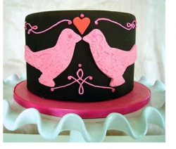 Trendy valentine cake in black with two pink birds kissing and a red heart in the center.PNG