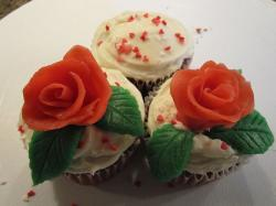 Three valentine's day theme cupcakes with red roses and white cream.JPG