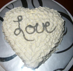 White valentine cake with big love word in silver.PNG
