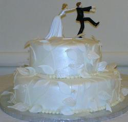 Two tier wedding cake with funny cake topper of bride catching groom.JPG