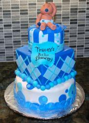 Three tier baby shower cake in white and blue with baby topper and hankerchief.JPG