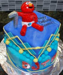 Blue birthday cake with two tiers and red Elmo topper with diaper topper.JPG