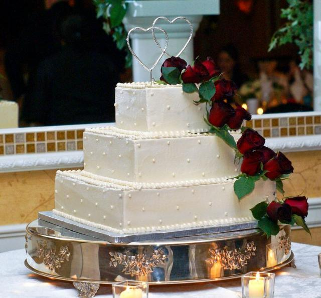 Three Tier Square Ivory Wedding Cake With Red Roses And Two Silver Heart Topp