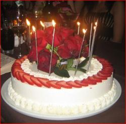 Strawberry and cream birthday cake with real red roses on top and tall candles.jpg