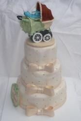 Three tier baby shower cake with baby carriage on top.JPG