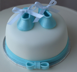 Baby shower mini cake with baby boy shoes cake topper in blue and white cake.PNG
