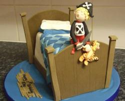 Kid in pirate costume on bed cake.JPG