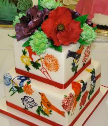 Two tier white cake with various birds and flower toppers.JPG