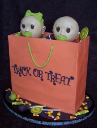 Halloween baby shower cake with two babies inside a trick or treat bag with full of candies.PNG