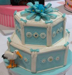 Baby blue two tier baby shower cake with bow and stork.JPG