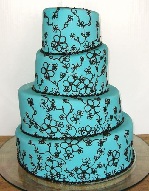 Four tier cyan wedding cake topsy-turvy style with branches.JPG