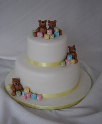 Teddy Bear Baby Shower Cake in cream white with yellow ribbons and full of cubes baby toys.PNG