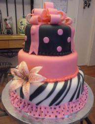 Three tier baby shower cake in pink black and white with pink bow and dress skirt.JPG