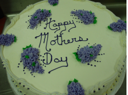 White Happy Mother's Day cake with purple floral cake decor.PNG