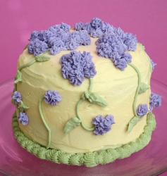 yellow cake for mother's day with purple flowers.PNG