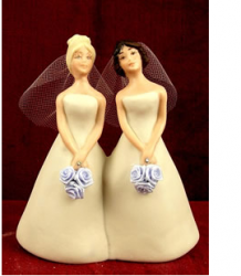 Picture of lesbian wedding cake toppers in their pretty light yellow bride gowns.PNG