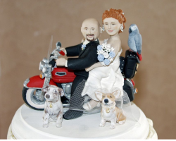 Pictures of funny cake toppers with bride and groom on motor bike surrounding with their pets.PNG