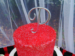 Red sugar coated wedding cake with cake topper monogram.PNG