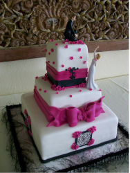 Romantic theme wedding cake with groom on very top tier and bride on the second tier looking up.PNG