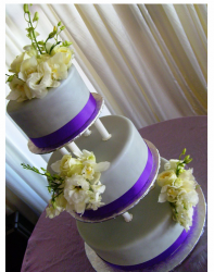Three tier wedding cake with bright purple ribbons and white fresh flowers.PNG